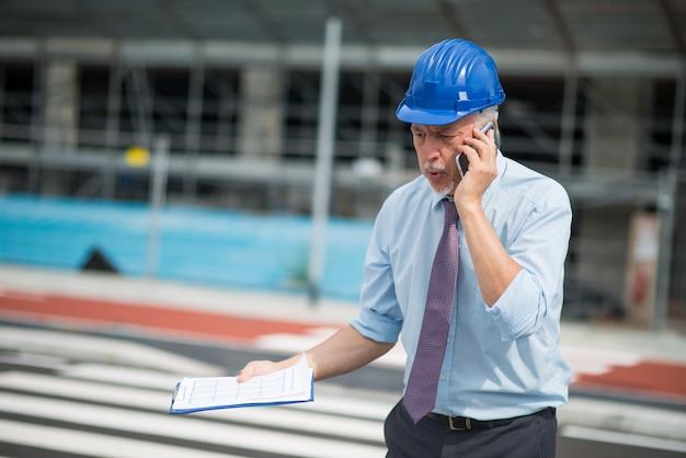 Arquiteto irritado, falando no celular na frente do canteiro de obras