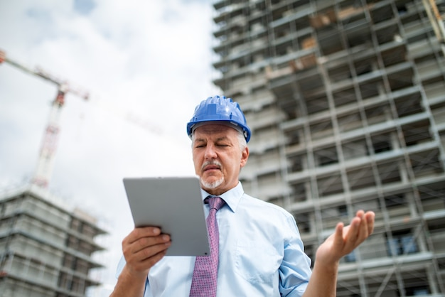 Arquiteto irritado usando seu tablet na frente de um canteiro de obras