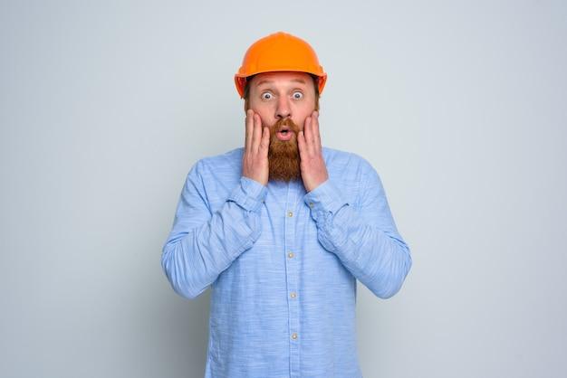 Arquiteto isolado surpreso com barba e capacete laranja