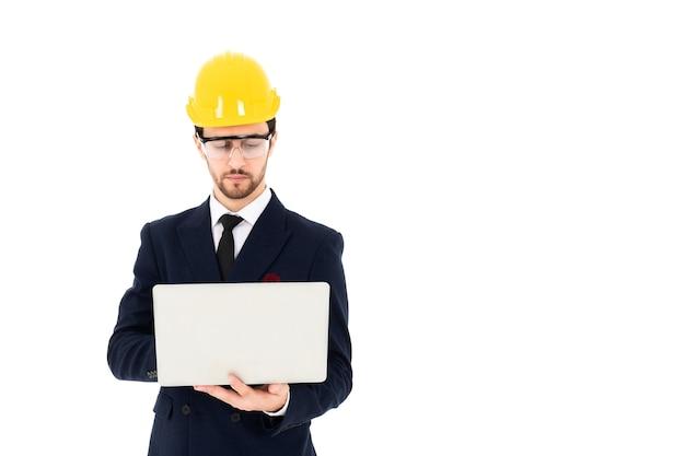 Arquiteto jovem inteligente usando óculos e capacete de segurança amarelo com as mãos segurando um laptop para verificar seu trabalho planejado. parede isolada branca de imagem para banner.
