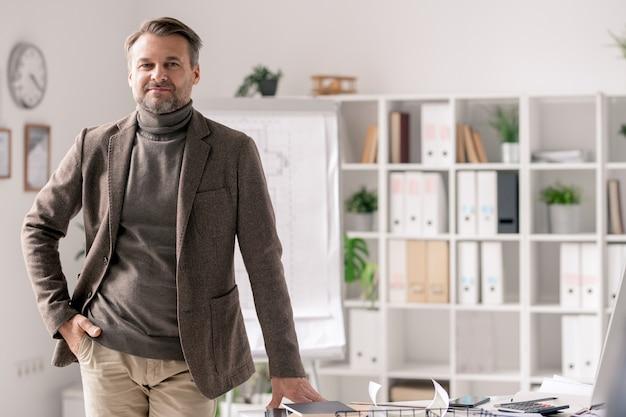 Arquiteto maduro confiante em trajes formais em pé ao lado da mesa no escritório no fundo das prateleiras com documentos