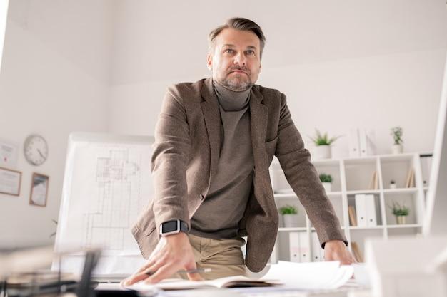 Arquiteto maduro pensativo encostado em uma mesa com papéis enquanto planeja o trabalho e faz anotações