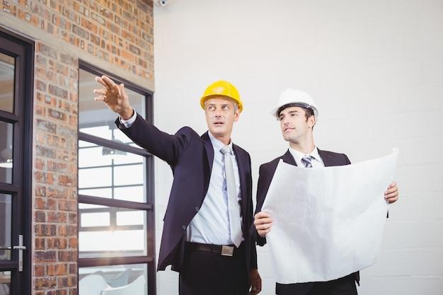Arquiteto masculino com colega segurando blueprint