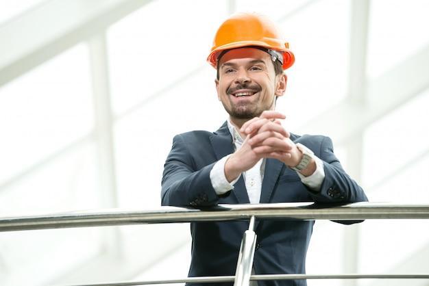 Arquiteto masculino de sorriso novo no escritório moderno.