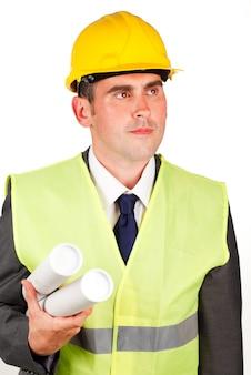 Arquiteto masculino que detém planos e que usa um chapéu duro