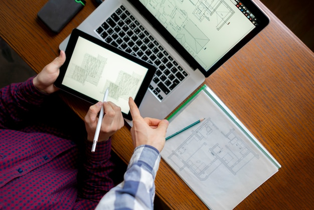 Arquiteto masculino trabalha com computador na mesa de madeira