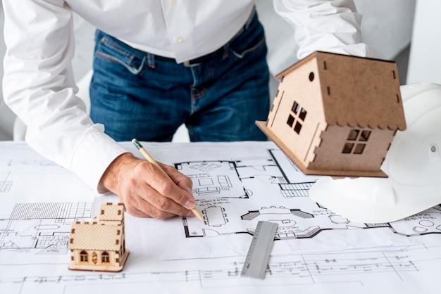 Arquiteto mostrando projetos em miniatura