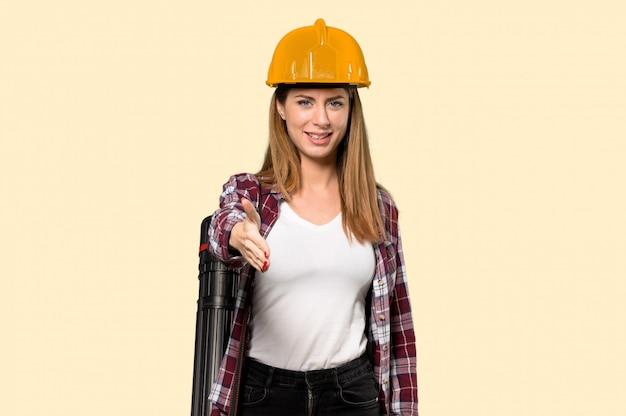 Arquiteto mulher apertando as mãos para fechar um bom negócio sobre amarelo isolado