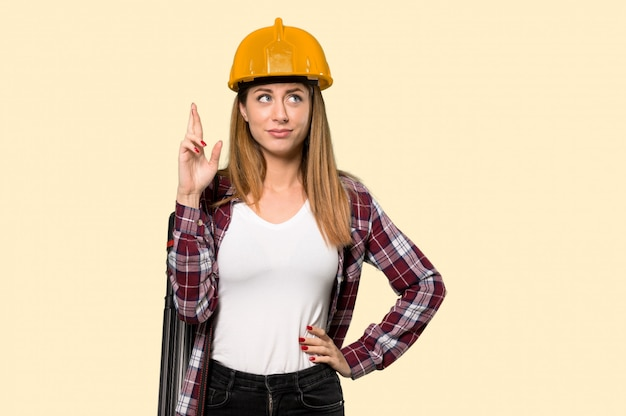 Arquiteto mulher com os dedos cruzando e desejando o melhor sobre amarelo isolado
