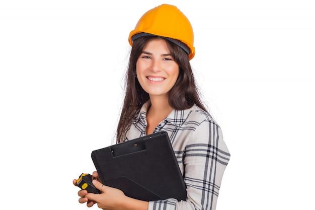 Arquiteto mulher usando capacete de construção e segurando pastas.