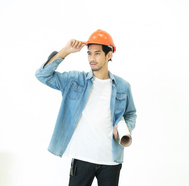 Arquiteto novo asiático homem mão toque laranja cor capacete olhando para longe, mantendo plantas isoladas em branco