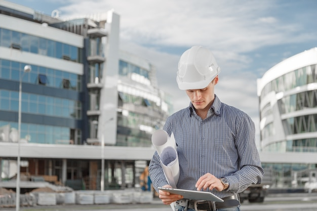 Arquiteto ou engenheiro-chefe usa tablet digital no canteiro de obras