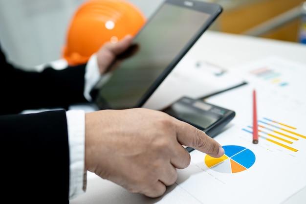 Arquiteto ou engenheiro, trabalhando com contabilidade de projeto com gráfico e capacete de construção no escritório, conceito de conta de construção.