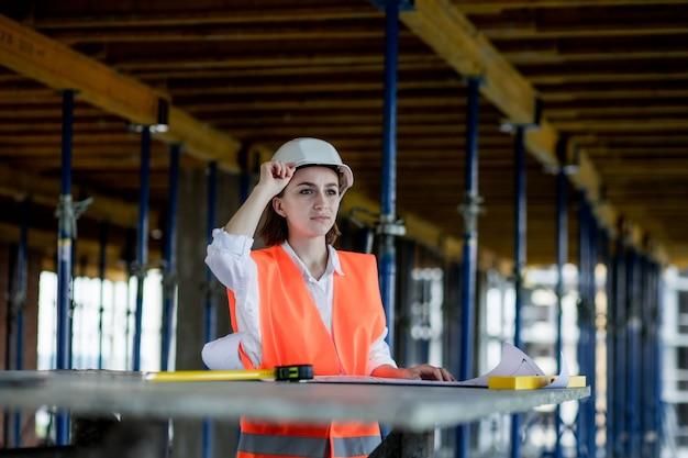 Arquiteto ou engenheiro trabalhando, navegando no interior do projeto de construção do canteiro de obras com o plano de planta. engenheiros de construção de mulher ou arquitetos que trabalham pessoas.