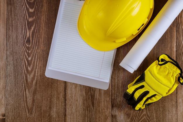 Arquiteto ou engenheiro trabalhando no modo de arquitetura do projeto no bloco de notas do escritório com capacete de segurança amarelo