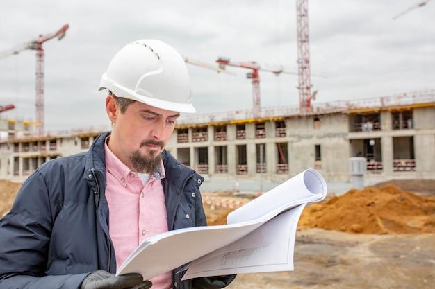 Arquiteto ou supervisor bonito ao ar livre em uma construção segurando uma planta nas mãos