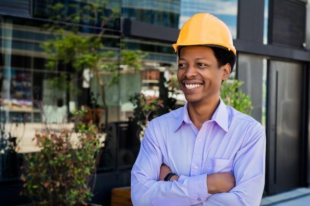 Arquiteto profissional com capacete amarelo ao ar livre.