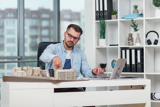 Arquiteto profissional em escritório inspeciona o projeto de um complexo residencial e faz