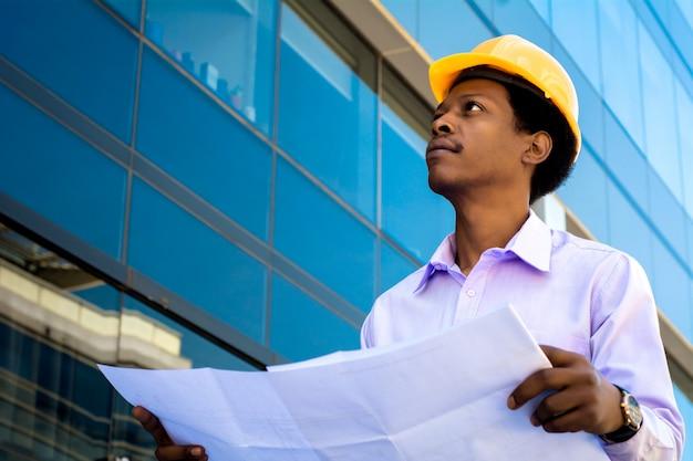Arquiteto profissional no capacete, olhando para longe