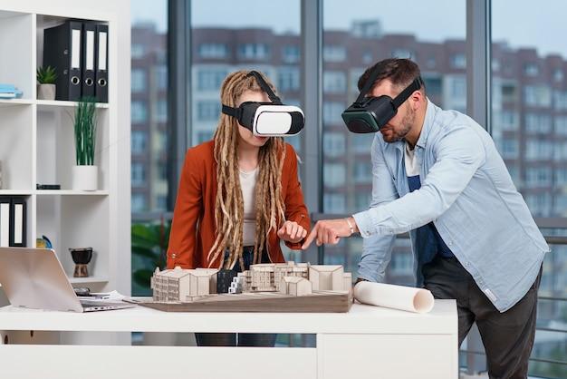 Arquiteto profissional trabalhando em uma mesa de escritório e usando um fone de ouvido vr, ele está visualizando uma interface de realidade virtual