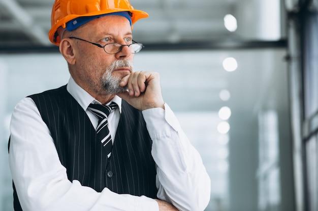 Arquiteto sênior do homem de negócios em um capacete