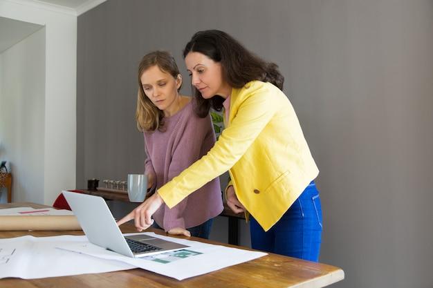 Arquiteto sério que mostra o projeto da casa na tela do laptop