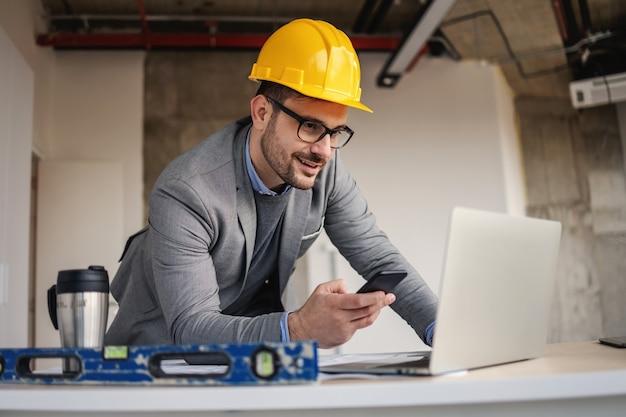 Arquiteto sorridente apoiado na mesa no canteiro de obras, olhando para o laptop e usando o telefone para contar aos colegas sobre o projeto.
