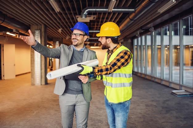 Arquiteto sorridente mostrando obras no local, mas o trabalhador da construção civil não está satisfeito.