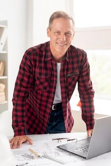 Arquiteto sorridente posando em sua mesa