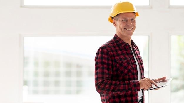 Arquiteto sorridente segurando um tablet com espaço de cópia