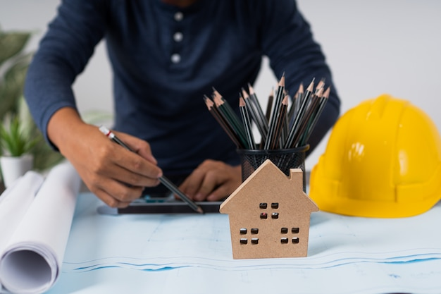 Arquiteto trabalhando e planejando na planta, objetos de engenharia no local de trabalho com laptop