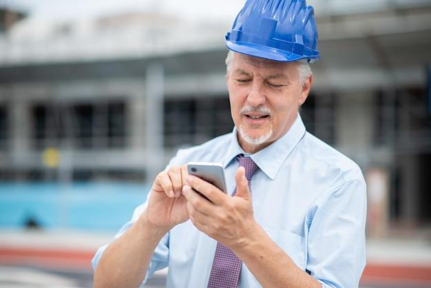Arquiteto usando seu celular na frente de um canteiro de obras