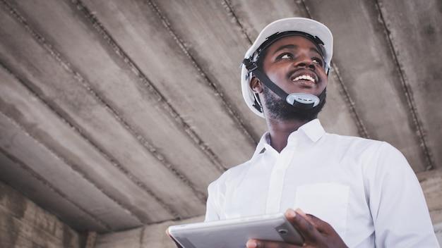 Arquitetos africanos engenheiro homem com tablet trabalham juntos no interior do canteiro de obras