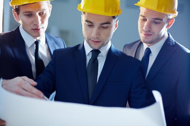 Arquitetos com capacetes analisando o plano