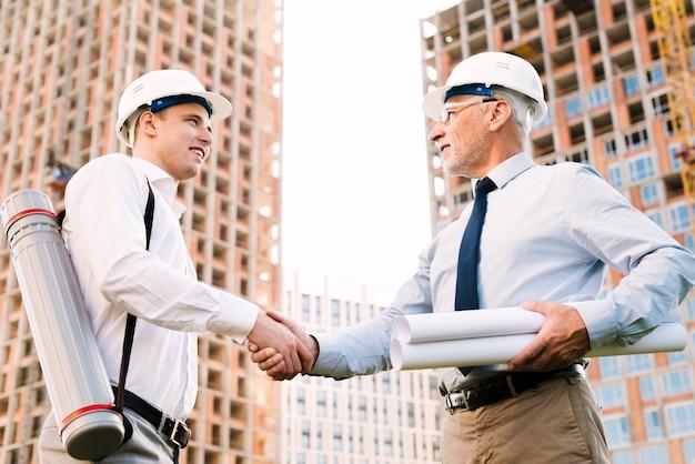 Arquitetos de baixo ângulo, apertando as mãos