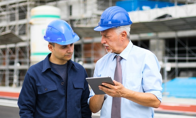 Arquitetos desenvolvedores revisando planos de construção no canteiro de obras usando um tablet