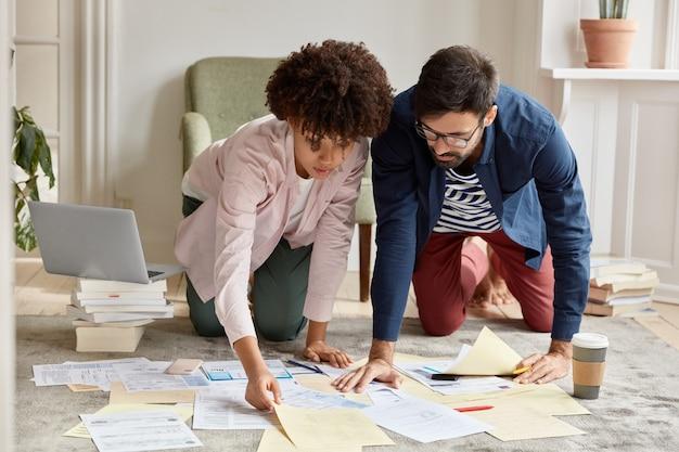 Arquitetos desenvolvem projeto futuro posando no chão da sala de estar