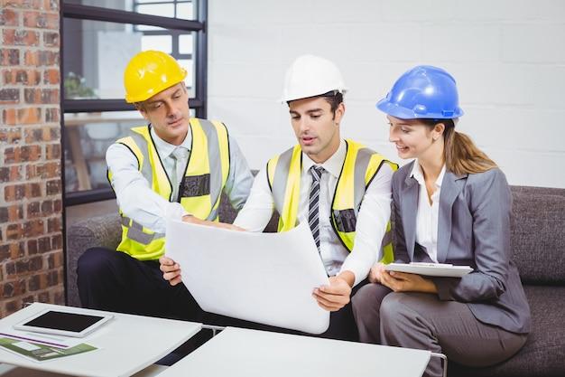 Arquitetos discutindo com blueprint
