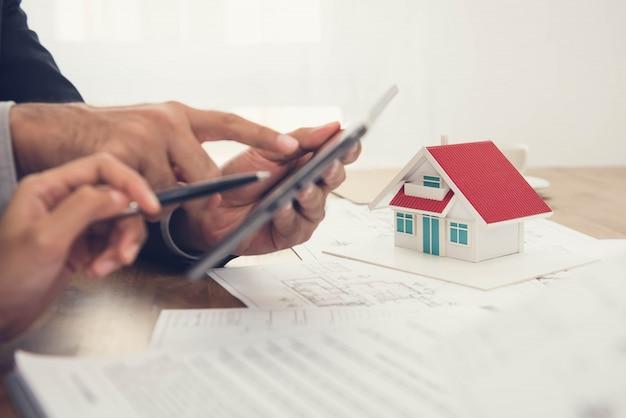 Arquitetos discutindo os planos para um modelo de casa