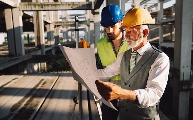 Arquitetos e engenheiros de construção ou topógrafos discutem planos e projetos