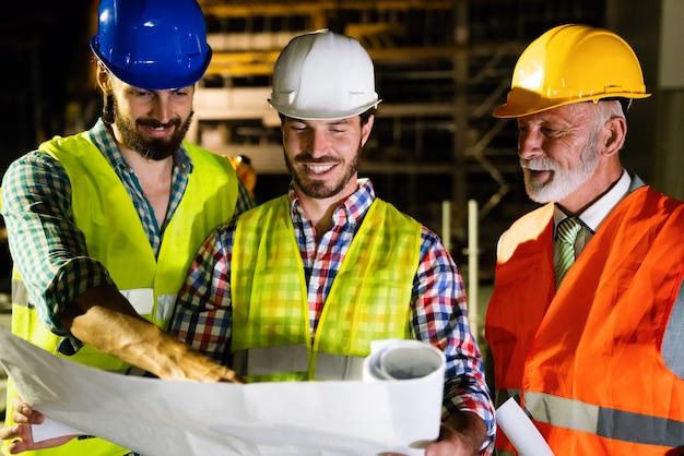 Arquitetos e engenheiros do sexo masculino analisando projeto no canteiro de obras