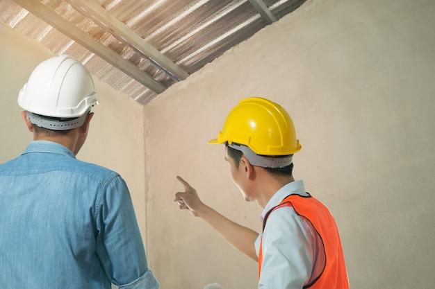 Arquitetos e engenheiros examinam o interior da casa para criar um plano de construção de sucesso