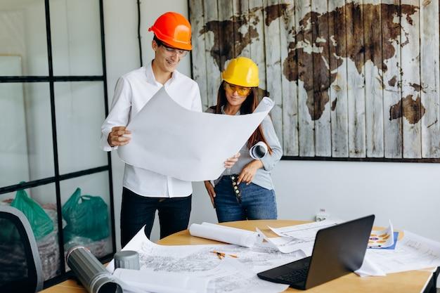 Arquitetos em capacetes olha planta no escritório
