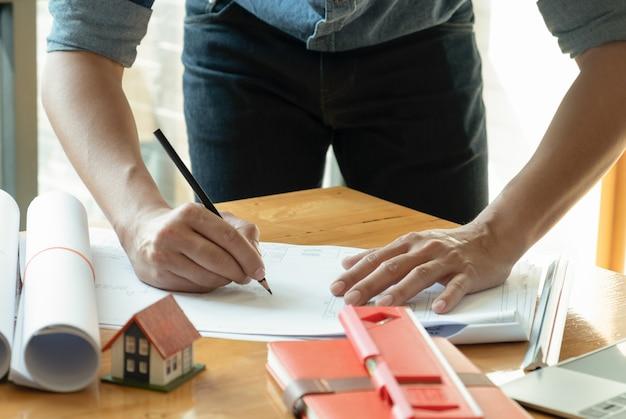 Arquitetos escrevem desenhos de casa na mesa.
