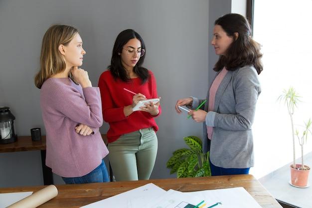 Arquitetos femininos sérios trabalhando e discutindo questões