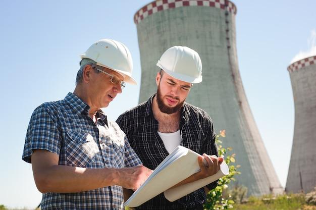 Arquitetos masculinos revisando documentos juntos em energia elétrica
