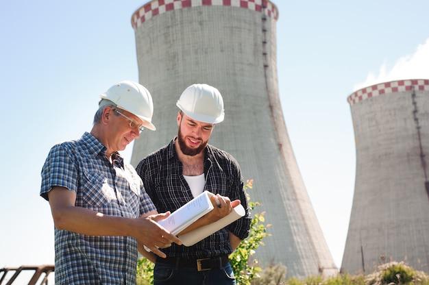 Arquitetos masculinos revisando documentos juntos na usina elétrica.