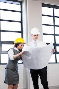 Arquitetos olhando planta no escritório
