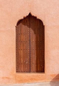 Arquitetura árabe tradicional, porta de madeira de estilo muçulmano e parede de barro vermelho