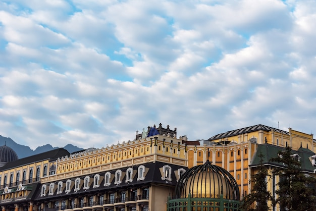 Arquitetura contra o meio-dia das nuvens do céu azul e do branco.